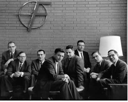 8 men in suits smiling at the camera